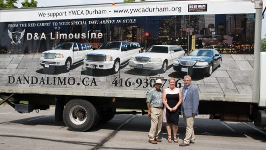 An image showing Mayor David Ryan, Angela Baltkois and Edward LAm in from of a D&A Limo Ad on the side of a big rig trailer
